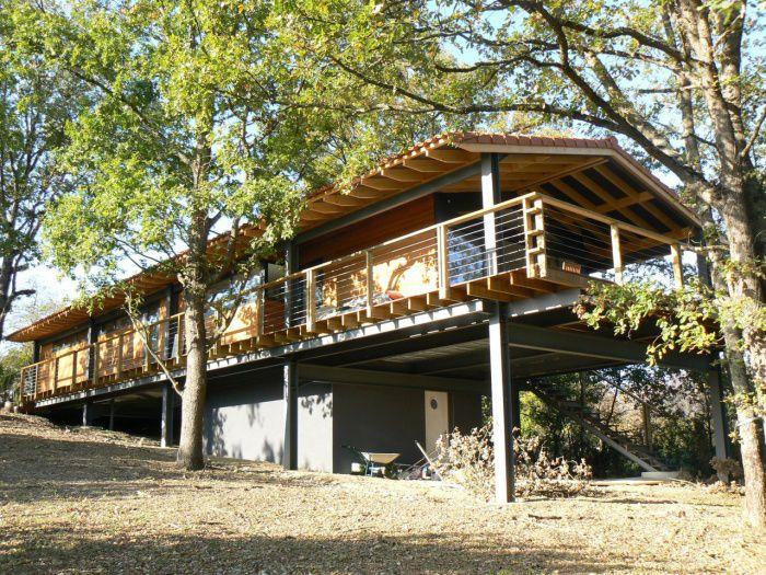 Vue extérieure d'une maison bois sur pilotis insérée dans la pente conçue par Acedo Architectes